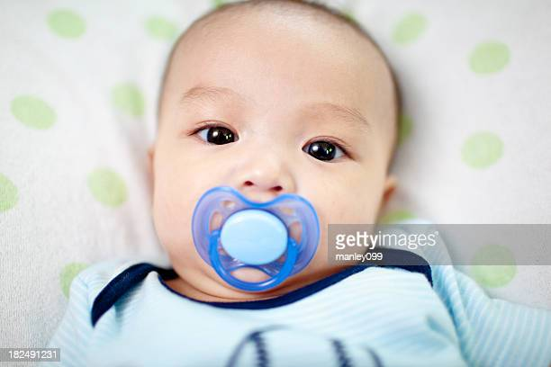baby boy with pacifier looking into camera