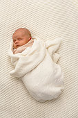 Baby boy (0-3 months) wrapped in blanket, sleeping