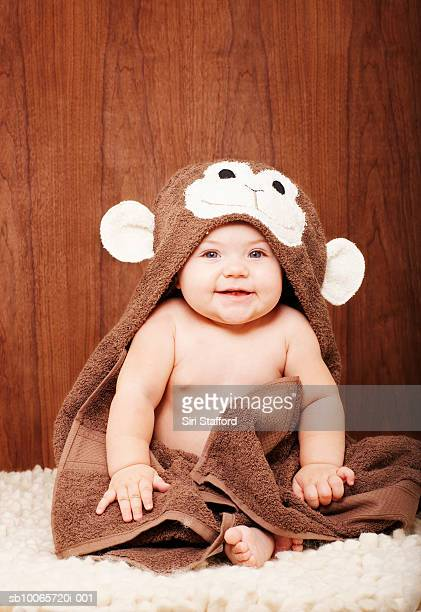 Baby boy (6-9 months) wrapped in hooded towel, portrait