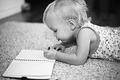 Little 2-year-old boy lying on the carpet and writing in his notebook. Concentration, attention, learning. Learning how to draw and write. Drawing with a pencil