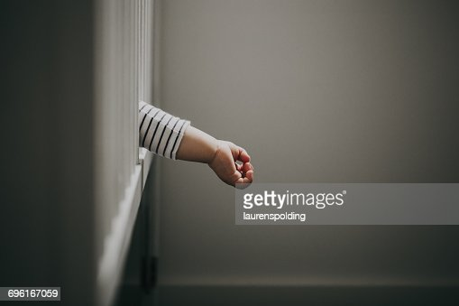 Baby boys hand hanging out of cot