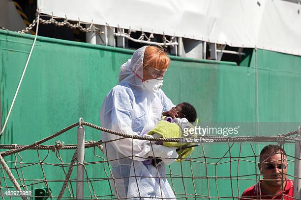 A baby carried by medical staff out from the vessel The Doctors Without Borders ship arrived at the port of Palermo carrying the bodies of four women...