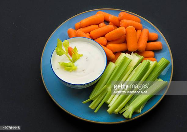 Baby carrots celery sticks and a bowl full of delicious ranch sauce garnished with celery sprig placed in a blue plate against a black background