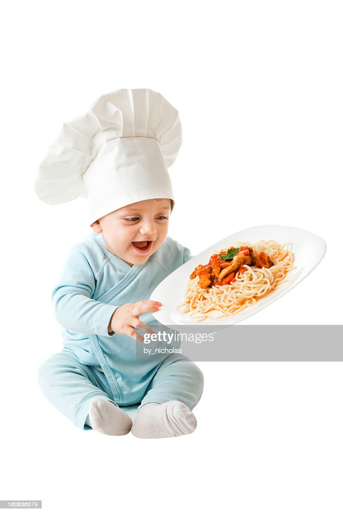 Baby chef holding a plate with spaghetti : Stock Photo