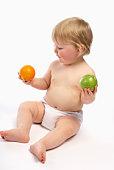 Baby choosing between apple and orange