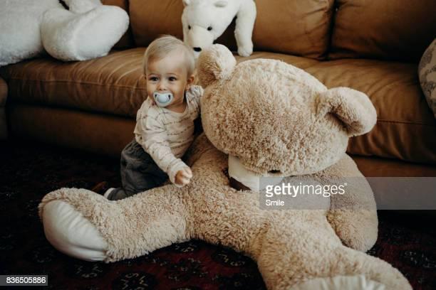 Baby climbing on large brown teddy bear