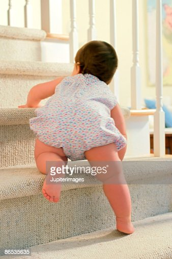 Baby climbing up stairs : Stock Photo
