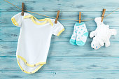 Baby clothes and white bear toy on a clothesline, wooden background