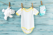 Baby clothes and white bear toy on a clothesline, blue wooden background
