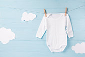 Baby clothes and white clouds on a clothesline, blue wooden background