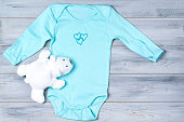 Baby clothes and white toy bear on a grey wooden background