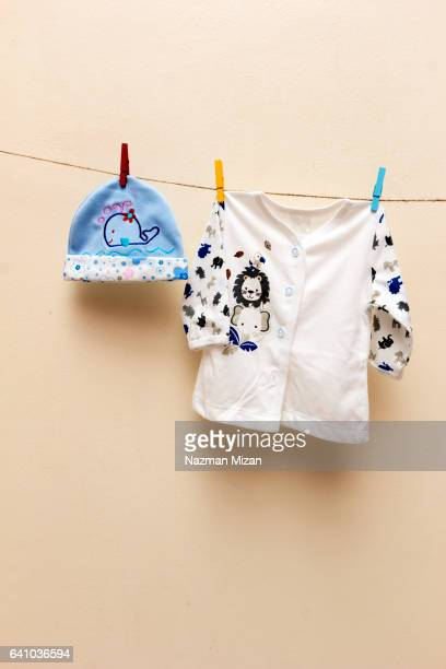 Baby clothes hanging on clothesline on light yellow background. Shot in portrait format.