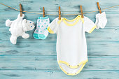 Baby boy clothes, onesie with socks and white bear toy on a clothesline