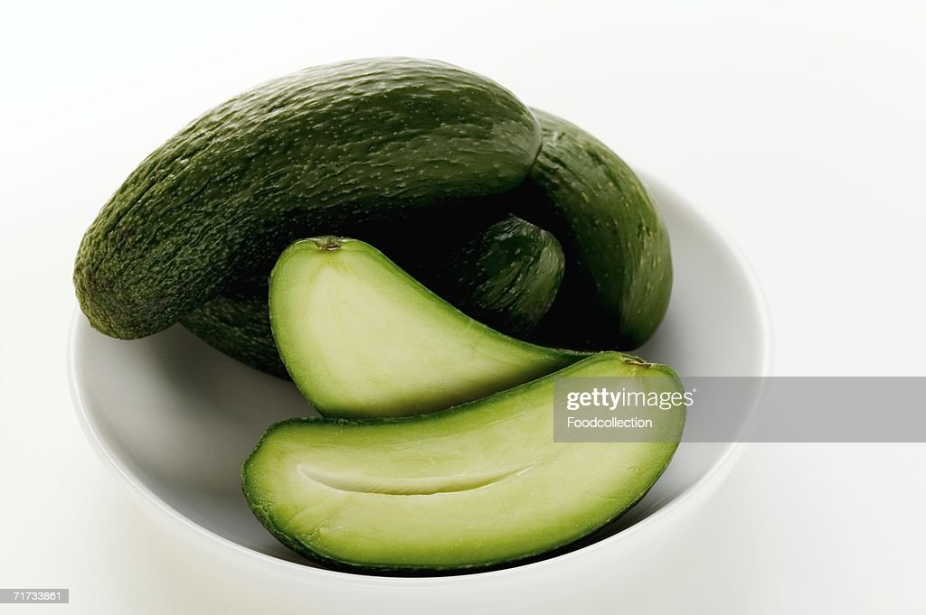 Baby courgettes, one halved, in bowl : Stock Photo