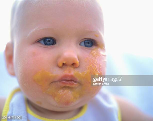 Baby (9-12 months) covered in baby food, close-up