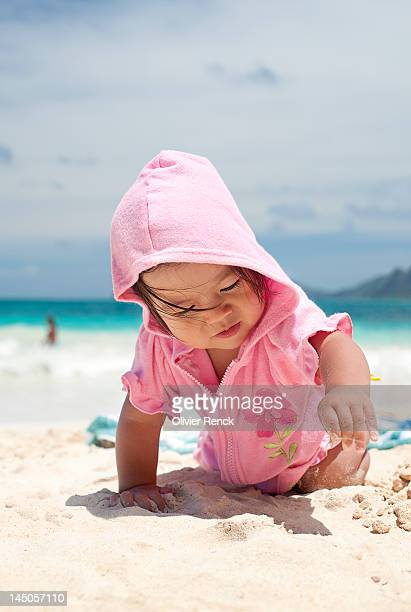 A baby crawling in the sand at the beach in Waimanalo, Hawaii.