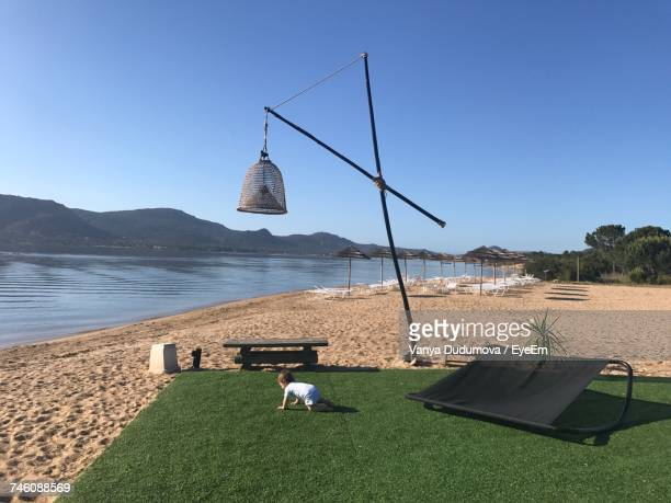 Baby Crawling On Turf At Beach Against Clear Sky