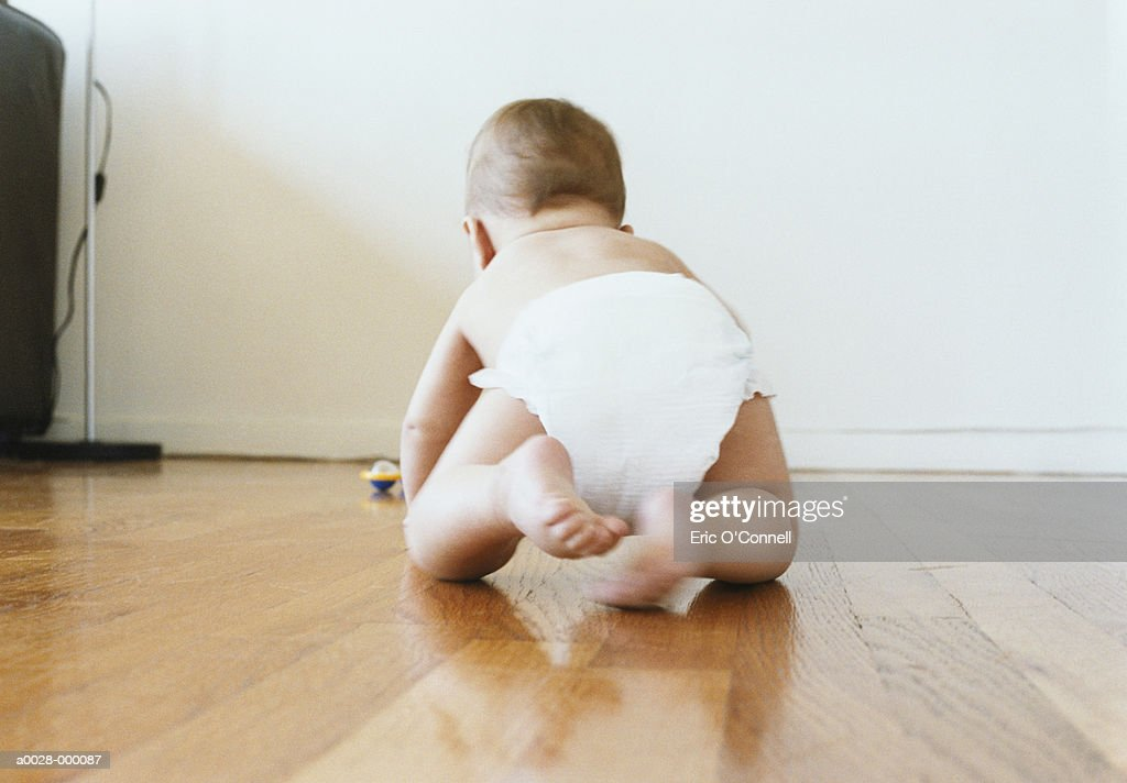 Baby Crawling on Wooden Floor : Stock Photo