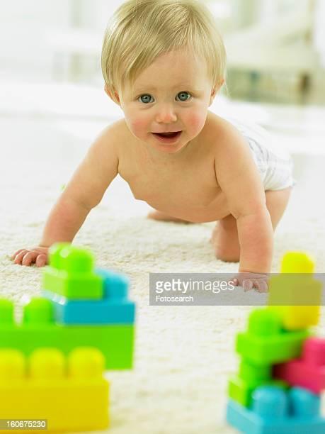 Baby crawling towards plastic blocks