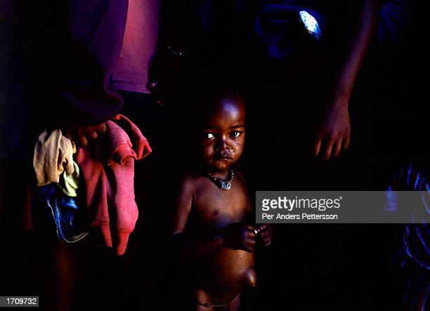 A baby cries after being measured by a health worker who teaches mothers about nutrition and health during a field visit June 27 2001 in Site B...