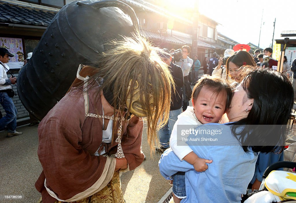 A baby cries as a man wearing ogre mask approaching during the Ueno Tenjin Festival on october 24, 2012 in Iga, Mie, Japan.