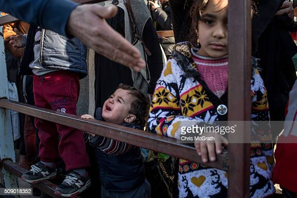 A baby cries while refugees wait in line to pass through the border gate to Syria as a small number of Syrian refugees were allowed to return to...