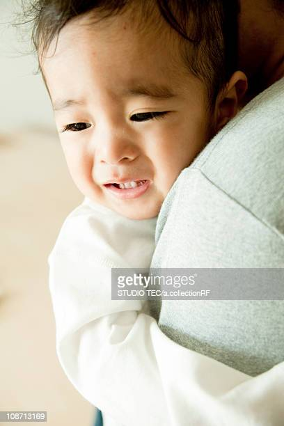 Baby crying and hugging Father