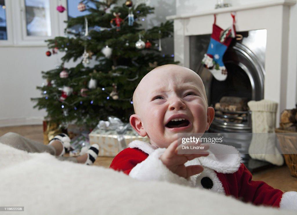 A baby crying at Christmas : Stock Photo