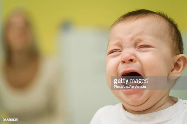 Baby crying, mother in background