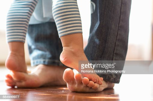 Baby daughter standing on fathers feet