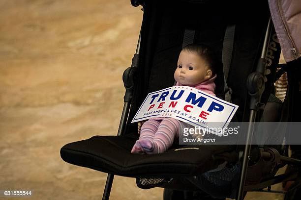 A baby doll in a stroller with a 'Trump/Pence' bumper sticker is pushed through the lobby at Trump Tower January 12 2017 in New York City...