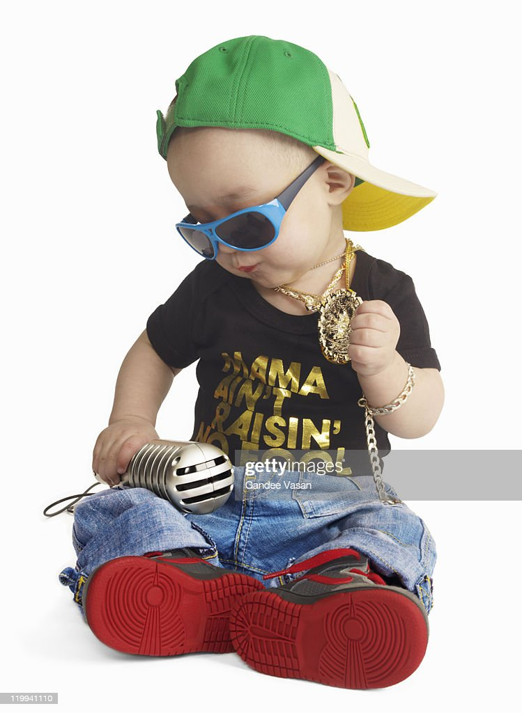 Baby dressed as urban rapper seated : Stock Photo