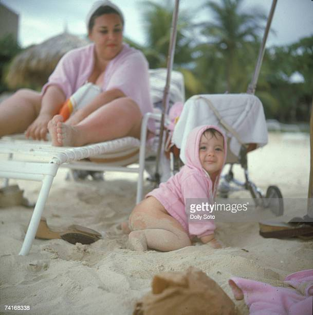 A baby dressed only in a pink hooded sweatshirt plays on the sand while a woman watches from a nearby deck chair Jamaica June 1979