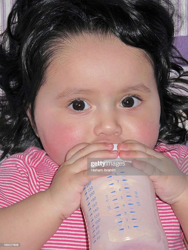 Baby drinking formula from a bottle : Stock Photo