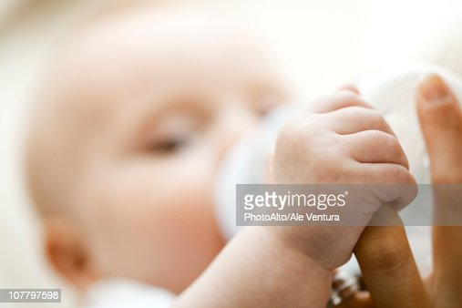 Baby drinking from bottle and holding mother's finger, close-up