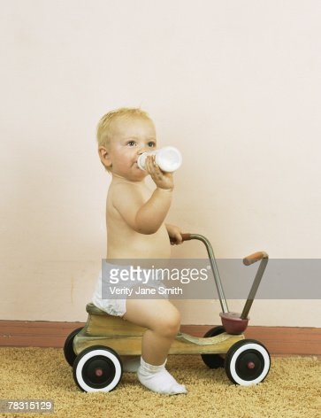 Baby drinking milk and sitting on toy scooter : Stock Photo