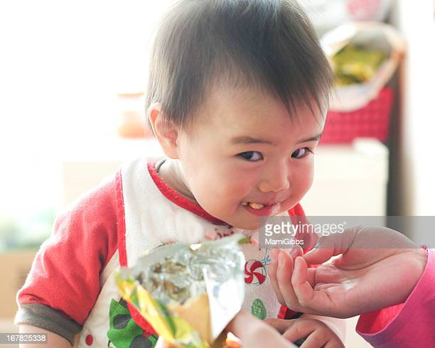 Baby eating a snack and smiling
