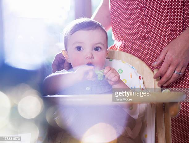 baby eating broccoli in high chair