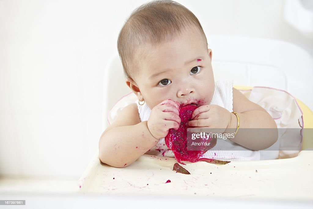 Baby eating dragon fruit : Stock Photo