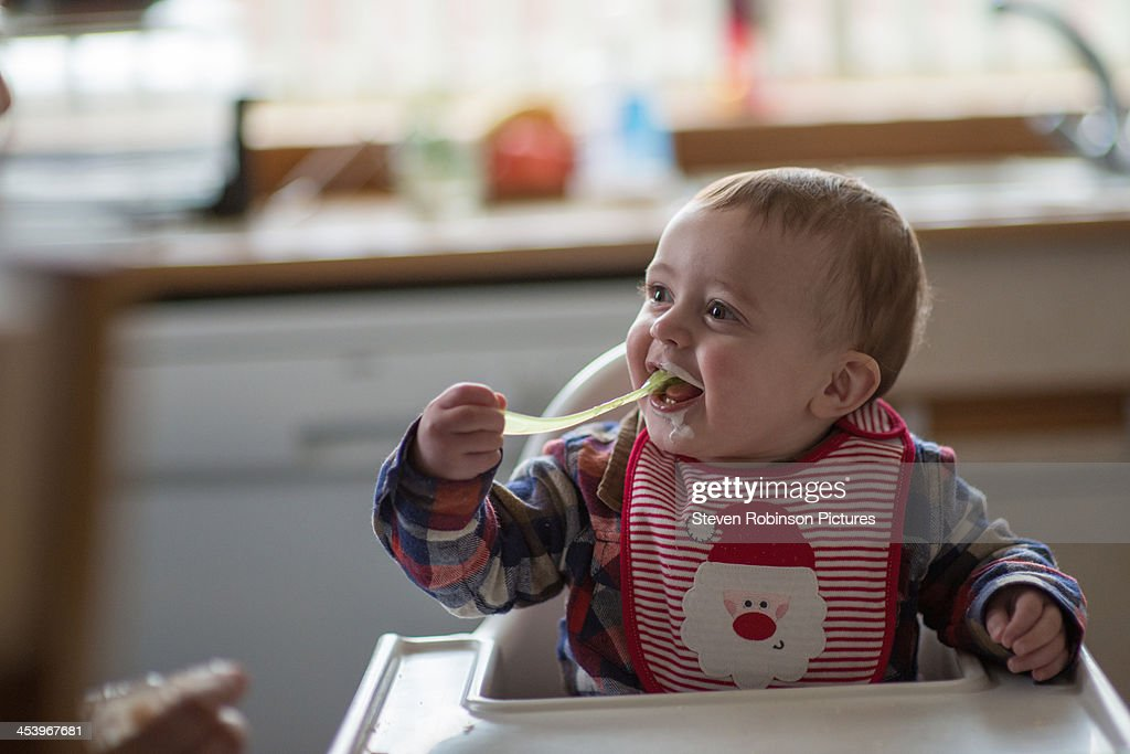 Baby eating with spoon himself for first time : Stock Photo