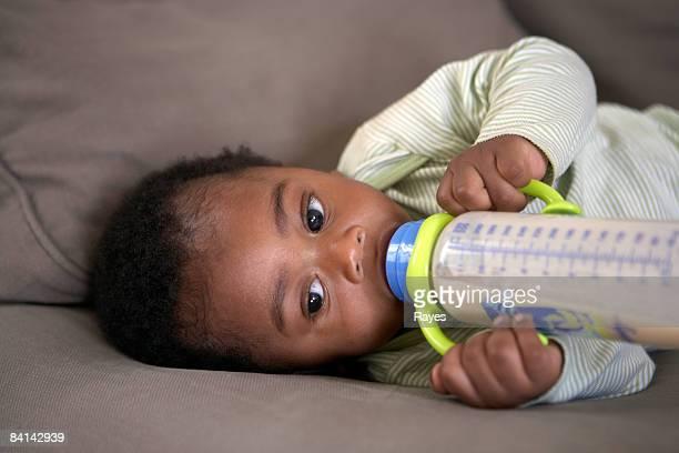 Bébé à nourrir lui-même une bouteille de lait