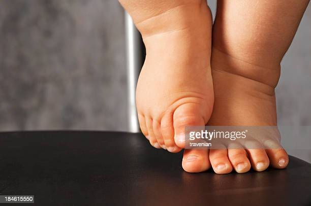 Baby feet on chair with one leg lifted