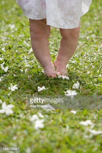 Baby feet walking on grass : Stock Photo