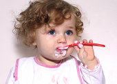 baby learning to feed herself with a spoon against white background