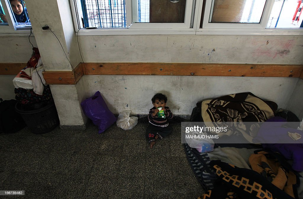 A baby from the displaced al-Attar family, who fled their house, eats breakfast as he sits on the floor of a classroom at a United Nations-run school in Gaza City on November 20, 2012. Israeli leaders discussed an Egyptian plan for a truce with Gaza's ruling Hamas, reports said, before a mission by the UN chief to Jerusalem and as the toll from Israeli raids on Gaza rose over 100.