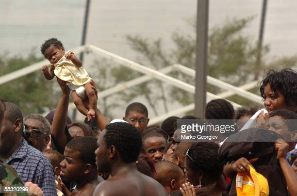 A baby gets lifted up from the crowd of people waiting to be evacuated from the New Orleans Super Dome on September 1 2005 in New Orleans Louisiana...