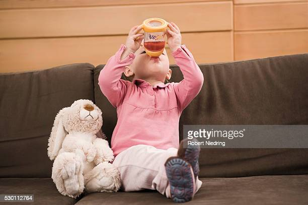 Baby girl 18 months sitting on sofa drinking juice