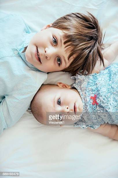 Baby girl and brother lying on bed