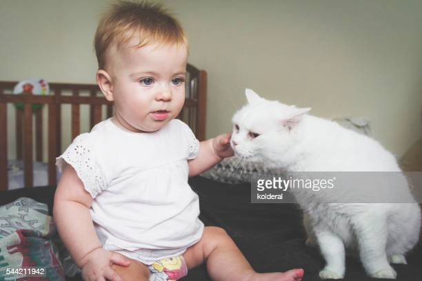 Baby girl and white pet cat