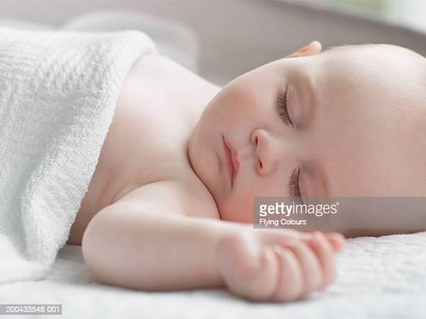Baby girl (6-9 months) asleep under blanket, close-up